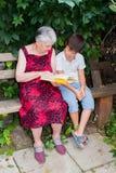 La mujer mayor con el grande-nieto leyó el libro Imágenes de archivo libres de regalías