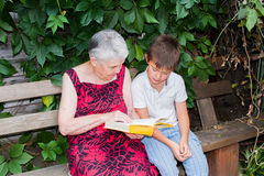 La mujer mayor con el grande-nieto leyó el libro Imagen de archivo
