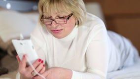 La mujer mayor con el smartphone blanco habla la mentira en la cama metrajes