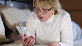 La mujer mayor con el smartphone blanco miente en la cama metrajes