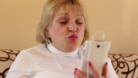 La mujer mayor con las negociaciones blancas del smartphone se sienta en el sofá metrajes