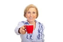 La mujer mayor da la taza de café roja Foto de archivo libre de regalías