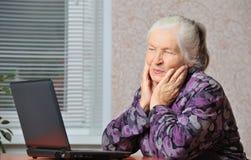 La mujer mayor delante de la computadora portátil Imagenes de archivo