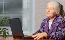 La mujer mayor delante de la computadora portátil Fotografía de archivo
