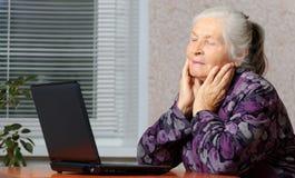 La mujer mayor delante de la computadora portátil Imagen de archivo libre de regalías