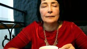 La mujer mayor elegante bebe té fresco caliente de una taza de cerámica blanca almacen de video