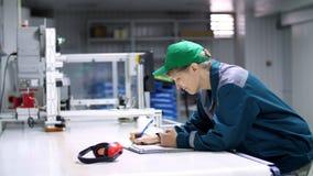 La mujer mayor, empleado, trabajador en una empresa, fábrica, llena un diario del servicio, libro de registro, trabajo industrial almacen de metraje de vídeo