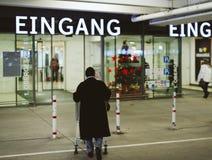 la mujer mayor empuja el carro del supermercado a la entrada de la tienda del edeka Imagenes de archivo