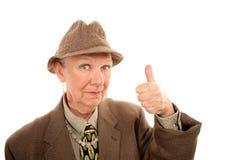 La mujer mayor en la fricción que da los pulgares sube gesto Imágenes de archivo libres de regalías