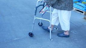 La mujer mayor en los pantalones blancos utiliza a un caminante mientras que camina en la acera almacen de video