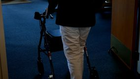 La mujer mayor en los pantalones blancos utiliza a un caminante almacen de metraje de vídeo
