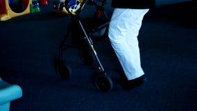 La mujer mayor en los pantalones blancos utiliza a un caminante mientras que camina en un edificio almacen de metraje de vídeo