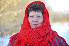 La mujer mayor en rojo hizo punto la bufanda en su cabeza fotografía de archivo