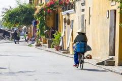 La mujer mayor en sombrero cónico está montando la bicicleta abajo de la calle de Ho Foto de archivo
