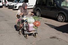 La mujer mayor en una silla de ruedas está dejando el mercado con la comida Foto de archivo