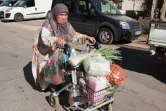 La mujer mayor en una silla de ruedas está dejando el mercado con la comida Fotografía de archivo libre de regalías