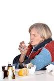 La mujer mayor enferma bebe el agua Fotografía de archivo