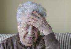 La mujer mayor enferma tiene dolor de cabeza Foto de archivo