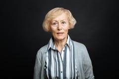 La mujer mayor enojada que expresaba descontento en el negro coloreó el estudio Imagenes de archivo