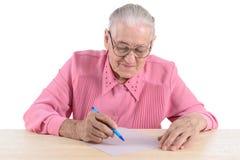 La mujer mayor escribe el documento Fotos de archivo