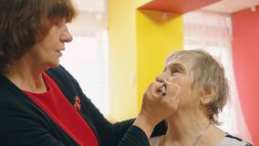 La mujer mayor est? haciendo el maquillaje para su amigo Aplicaci?n del l?piz de ojos para que ceja haga una forma almacen de metraje de vídeo