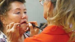 La mujer mayor est? pintando los labios de su amigo para el partido almacen de video