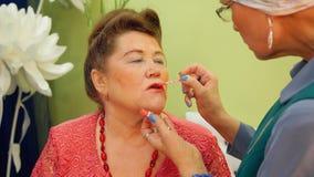 La mujer mayor está pintando los labios de su amigo para el partido con lustre del labio metrajes