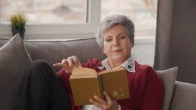 La mujer mayor está poniendo en el sofá y está leyendo historia interesante del amor verdadero y de la aventura hermosa almacen de video