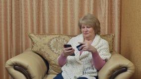 La mujer mayor feliz hace compras sobre Internet y paga con una tarjeta Compras en línea almacen de video