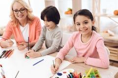 La mujer mayor hermosa enseña a niños a dibujar Drenaje de los niños con las pinturas Imagen de archivo libre de regalías