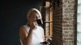 La mujer mayor hermosa está bebiendo el café en hora de la almuerzo en el trabajo La mujer madura atractiva está gozando del café almacen de metraje de vídeo