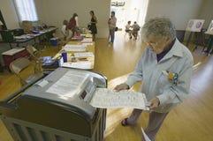 La mujer mayor inserta la votación terminada para la elección del congreso, noviembre de 2006, en un escáner electrónico en Ojai, Foto de archivo libre de regalías
