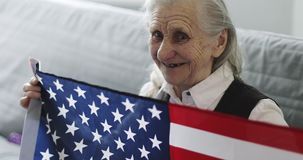 La mujer mayor linda con las arrugas se está sentando en el sofá y está sosteniendo la bandera americana en hogar almacen de video