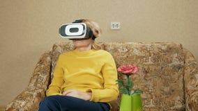 La mujer mayor lleva los vidrios de realidad virtual y de mirar una película Ella mira alrededor y quiere tocar el virtual almacen de video