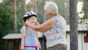 La mujer mayor lleva un casco protector por sus 6 años de la hija El cuidado y la protección del concepto del ` de los padres metrajes