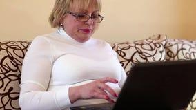 La mujer mayor mecanografía el texto usando el ordenador portátil Mujer con el cuaderno metrajes