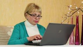 La mujer mayor mecanografía el texto usando el ordenador portátil Mujer con el cuaderno almacen de video