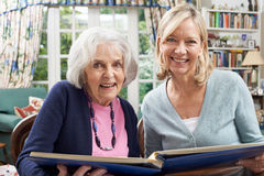 La mujer mayor mira el álbum de foto con el vecino femenino maduro Imágenes de archivo libres de regalías