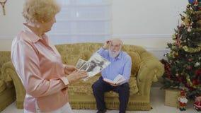 La mujer mayor mira sus fotos viejas, su libro leído marido que se sienta en el sofá almacen de metraje de vídeo