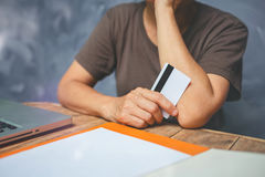 La mujer mayor muestra su tarjeta de crédito en la tabla de madera vieja con gris fotografía de archivo libre de regalías