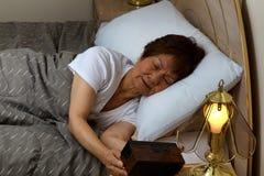 La mujer mayor no puede dormir en la noche mientras que mira el reloj Foto de archivo libre de regalías