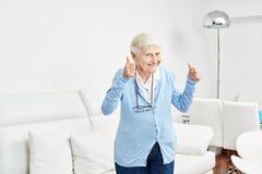 La mujer mayor optimista guarda sus pulgares para arriba fotografía de archivo