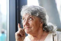 La mujer mayor pensativa destaca un finger fotografía de archivo libre de regalías