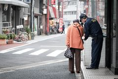 La mujer mayor pide la dirección de una policía en la calle de Japón foto de archivo