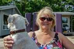 La mujer mayor positiva está disfrutando de tiempo con su perro imagen de archivo