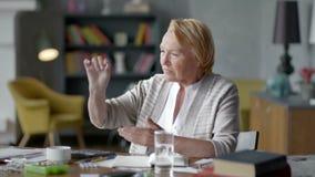 La mujer mayor preocupada infeliz mira incrédulamente una píldora no quiera tomar las drogas médicas almacen de metraje de vídeo