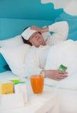La mujer mayor puso enfermedad en la cama con el medicamento y las almohadas, fotografía de archivo