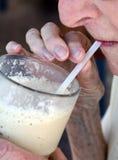 La mujer mayor que bebía un bridella condimentó el batido de leche con una paja Imagenes de archivo