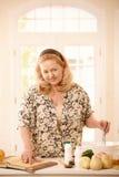 Mujer que comprueba receta en cocina Imágenes de archivo libres de regalías
