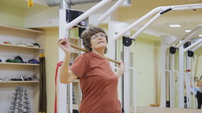 La mujer mayor que da vuelta con el palillo, haciendo la fisioterapia ejercita en sitio de la aptitud Gimnasia sana Mayores activ metrajes